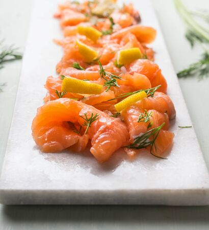 Close up of slices of homemade smoked salmon with dill and lemon served on marble cutting board on light background. Top view. Healthy food