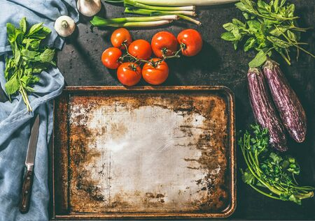 Cooking of vegetarian dish with tomatoes, eggplants, parsley, mint onions and garlic on rustic background and vintage baking sheet. Place for  your design Zdjęcie Seryjne