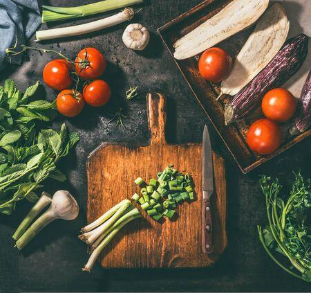Vegetarian ,cooking ,concept,  Chopped, ingredients ,wooden ,cutting board, Various ,vegetables, leek, tomatoes, eggplants , garlic ,herbs ,n dark, rustic, background, top view Zdjęcie Seryjne