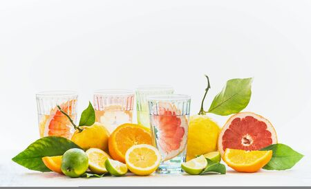 Various healthy summer lemonade in glasses with variety of organic citrus fruits: lime, oranges, grapefruit and lemon on table at white background. Infused water. Copy space. Vitamin C concept Zdjęcie Seryjne