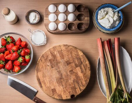 Food background frame with strawberries and rhubarb , eggs, cottage cheese around wooden cutting board. Top view. Seasonal cooking and baking. Healthy clean organic food.