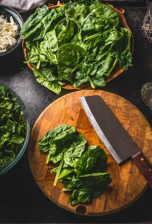 Fresh spinach on wooden cutting board with knife on dark rustic table background. Top view. Home cuisine. Tasty vegan cooking. Healthy food concept