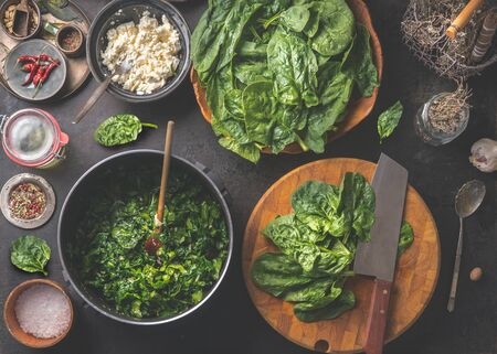 Tasty stewed spinach cooking preparation with cooking pot , ingredients and kitchen utensils. Wooden cutting board with knife. Seasoning and spices. Home cuisine. Top view. Healthy green food Zdjęcie Seryjne