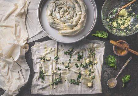 Backing preparation of savory pie with phyllo dough sheets stuffed with spinach and feta cheese on dark rustic background . Top view. Balkan or oriental cuisine. Home cooking. Burek making. Pastry Stock fotó