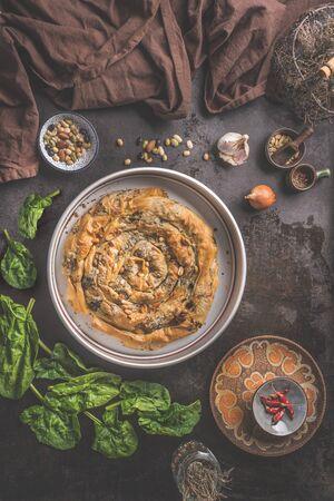 Tasty stuffed savory pastry pie with phyllo dough in traditional baking pan on dark rustic background with ingredients.  Top view. Balkan or oriental cuisine. Home cooking. Burek making. Ramadan food