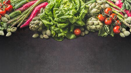 Variety of farm vegetables: lettuce , green almonds, asparagus,artichoke, radishes and cherry tomatoes on dark background. Healthy clean vegetarian food and  eating concept. Top view. Frame