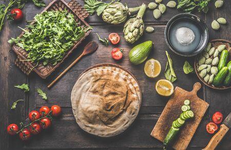 Various fresh ingredients around tortilla or flatbread for tasty vegan wraps making. Fresh salad ingredients: avocado, lemon, arugula, tomatoes, green almonds, artichokes on wooden background