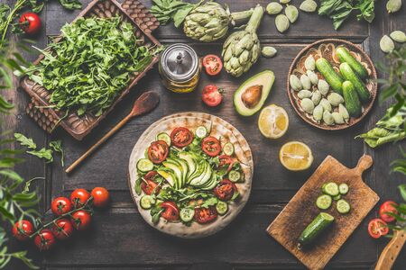 Healthy lunch making preparation. Tortilla wraps with fresh vegetables, avocado , olives oil and lemon on rustic wooden kitchen table , top view. Cooking preparation. Vegan food. Fresh ingredients Zdjęcie Seryjne