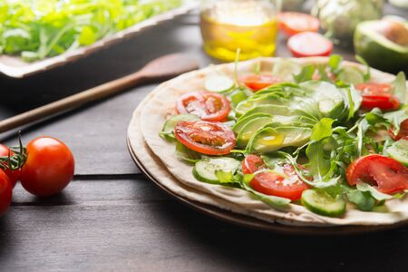 Tasty vegan tortilla wrap preparation. Close up of fresh salad vegetables with sliced avocado and olives oil on rustic table. Healthy clean food concept. Lunch idea. Summer food Zdjęcie Seryjne