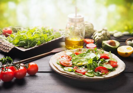 Fresh salad vegetables with sliced avocado and olives oil on tortilla on rustic table at sunny summer nature background. Tasty vegan tortilla wrap preparation. Healthy lunch concept. Summer food