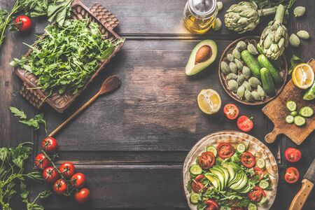 Food background with preparation and fresh ingredients of vegan tortilla wraps . Various fresh salad vegetables, avocado , olives oil and flatbread on dark rustic kitchen table. Healthy lunch Zdjęcie Seryjne