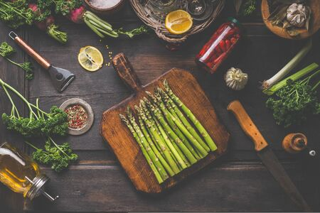 Fresh organic asparagus on wooden cutting board. Copped herbs, olive oil, lemon and seasonings. Preserved hot peppers in glass jar on dark rustic background, top view. Healthy lifestyle. Home cooking