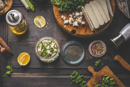 Marinated feta cheese cubed in olives oil with herbs, lemon and seasonings in jar on rustic wooden table with ingredients. Vintage cutting board and wooden cutlery. Home cooking preparation. Top view Zdjęcie Seryjne