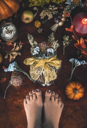 Cozy autumn mood at home. Female feet and vase with dried flowers arrangement on carpet floor with pumpkins, candles, and fall leaves. Top view Zdjęcie Seryjne