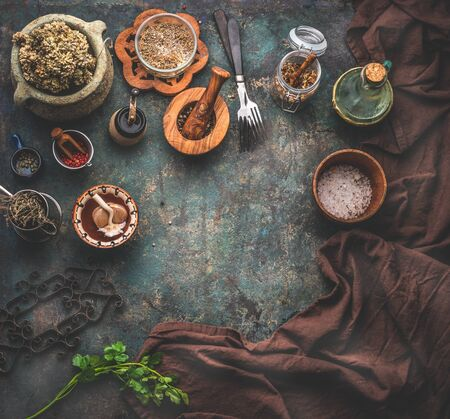 Rustic food background with vintage kitchen utensils. Herbs and spices in wooden bowls, olives oil and napkin. Frame. Top view. Copy space for your product or design