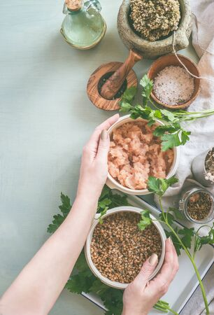 Female hands cooking preparation on light kitchen tables with bowls and fresh seasoning. Woman hands holding bowls with ingredients. Top view Zdjęcie Seryjne