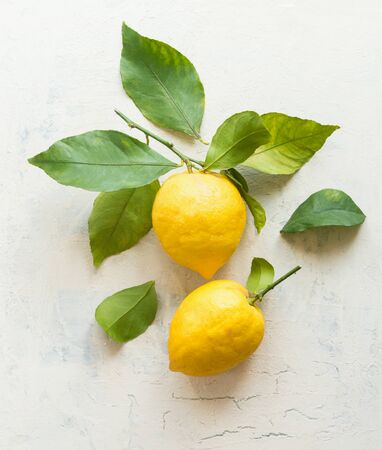 Ripe lemons with green leaves  composition on white desktop background , top view. Organic citrus fruits. Flat lay. Healthy food concept.