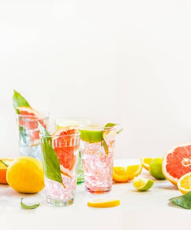 Glasses with iced citrus fruits  lemonade on white table with various ingredients. Summer drinks. Healthy  beverages. Zdjęcie Seryjne
