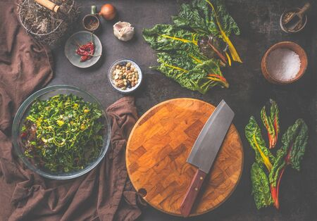 Rustic vegetarian food background with blank cutting board, knife and colorful chard leaves for vegetarian cooking. Top view. Rural cuisine style. Zdjęcie Seryjne