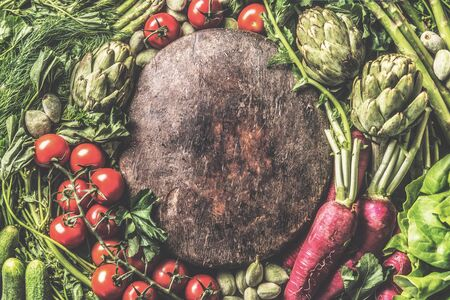 Various  vegetables around vintage wooden plate. Top view. Frame made with organic veggies. Healthy clean food concept