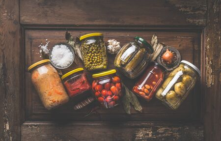 Homemade marinated and pickles vegetables preserve in jars on rustic wooden background with herbs and spices. Top view. Garden harvest caning . Home cuisine. Fermented food Zdjęcie Seryjne