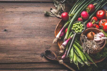 Food background with healthy vegetarian ingredients on rustic wooden table with herbs and spices. Garden organic vegetables on wooden bowl. Top view. Paleo dieting. Vegan. Seasonal vegetables Zdjęcie Seryjne
