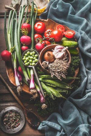 Top view of veggie plate. Vegetarian cooking ingredients with various organic vegetables from garden and wooden cooking spoon. Healthy clean food. Home cuisine. Paleo diet. weight loss eating