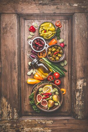 Tasty vegetarian or vegan food cooking ingredient with pickled vegetables, olives , olives oil, green organic almonds lemon and figs on vintage wooden background with kitchen utensils. Top view.