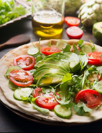 Cooking Delicious tortilla with cherry tomatoes, avocado, cucumber, arugula and olive oil. On a rustic wooden table, with ingredients laid out around. The idea of ​​a healthy dish. Close up. 스톡 콘텐츠