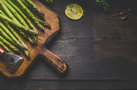 Fresh green asparagus with lemon on vintage wooden cutting board with copper peeler . Vegetarian healthy food. Rustic wooden background. Top view. Place for text.