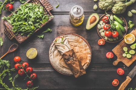 Vegetarian tortilla wraps preparation with ingredients: fresh vegetables. Plate with flat bread wrap on rustic wooden table background. Avocado, arugula, tomatoes, almond,cucumber.  Healthy lunch food