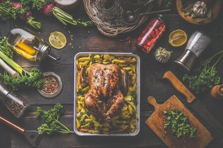 Tasty whole roasted chicken on baking tray with potatoes served on dark rustic kitchen table with cooking ingredients , canned and fresh vegetables , olives oil, lemon, herbs and spices. Top view. 스톡 콘텐츠