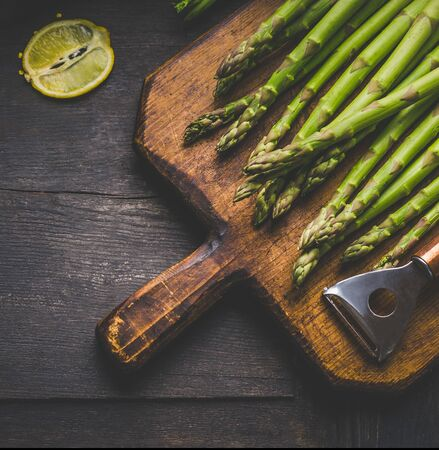 Vegetarian healthy concept. Fresh green asparagus with lemon on a vintage wooden cutting board. On a rustic wooden background. Top view. Close up. 스톡 콘텐츠