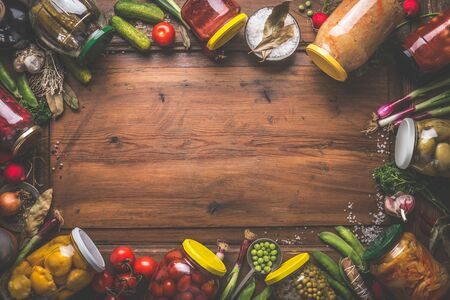 Wooden food background with various preserved vegetables in jars with fresh ingredients, top view. Frame or border. Place for your design. Homemade harvest canning. Fermented vegetables. Healthy food Zdjęcie Seryjne