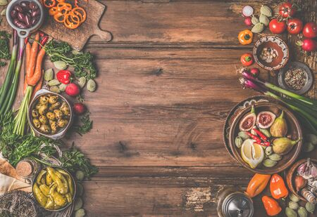 Healthy food and snack background. Bowls with tasty ingredients of Mediterranean cuisine: various vegetables, olives, pickled pepperoni and figs on wooden rustic table. Top view. Frame. Vegan food 스톡 콘텐츠