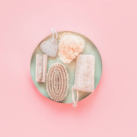 Eco friendly skin care and spa accessories on tray at pastel pink background, top view. Zero waste . Modern beauty concept. Blog layout. Plastic free. Natural body treatment equipment