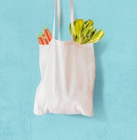 White  textile grocery shopping bag with vegetables hanging at light blue background. Copy space. Zero waste concept. Cotton reusable bag. Plastic free shopping. Eco friendly bag mock up.