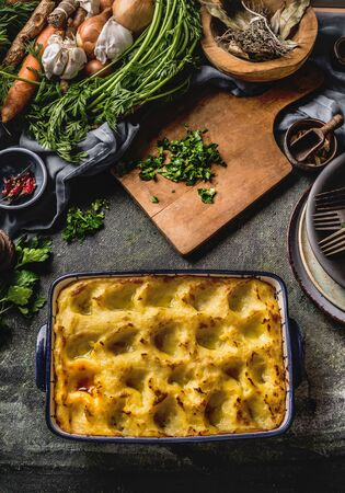 Potato casserole . Homemade cooking, farm meal food, Chopped greens on a wooden cutting board. Around lined with various vegetables and herbs. Top view. Tasty home cuisine Zdjęcie Seryjne - 147663888