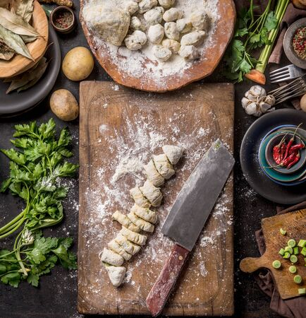 Homemade gnocchi preparation on rustic kitchen table with ingredients. Top view. Potatoes dough on wooden cutting board. Italian food concept. Standard-Bild