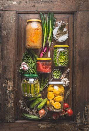 Various preserved vegetables in jars on rustic wooden background with ingredients, top view. Flat lay. Composition of canned food. Vegan. Home cuisine. Harvesting storage. Zero waste housekeeping Standard-Bild