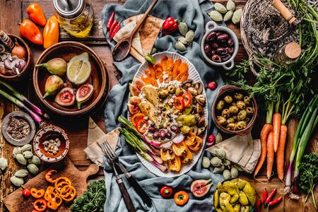 Tasty Mediterranean cuisine with healthy food with hummus plate. Ramadan iftar dinner. Various pickled and fresh  vegetables: olives, fids, green almond. Vegan party food Top view. Festive gathering 스톡 콘텐츠
