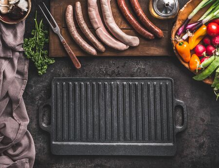 Grill or barbecue food background. Empty cast iron grill griddle and meat fork on rustic kitchen table. Various sausages on a wooden cutting board. Wooden bowl with vegetables. Top view.