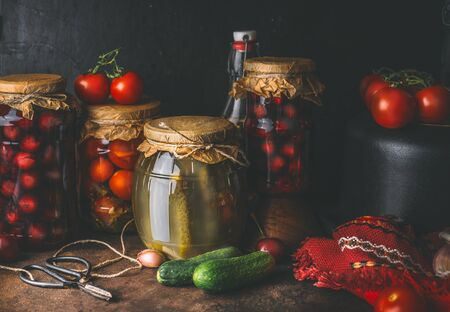 Harvest preserve concept. Glass jar with fermented pickled vegetables and fruits on dark rustic kitchen table with canned food for winter season. Canning and conservation of harvest.