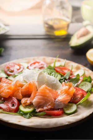 Tasty wrap bread with salmon, cheese, arugula, tomatoes and cucumbers. Flat bread with ingredients on a wooden table.  Close up. Healthy food concept. 스톡 콘텐츠