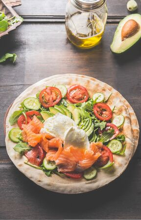 Tortilla with salmon,avocado, cheese, arugula, tomatoes and cucumbers. Flat bread with ingredients on a wooden table. Tortilla wrap preparation. Top view. Close up. Healthy snack or lunch food