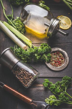 Seasoning and meals flavor concept for cooking vegetarian food. Parsley, pepper mill and oil on a rustic wooden table, close up. Home cuisine Stok Fotoğraf - 147670640
