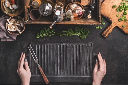 Grill or BBQ food background. Woman hold empty cast iron grill griddle and meat fork on roast rustic kitchen table. Wooden box with seasonings, oils and other kitchen utensils.Top view. Place for text