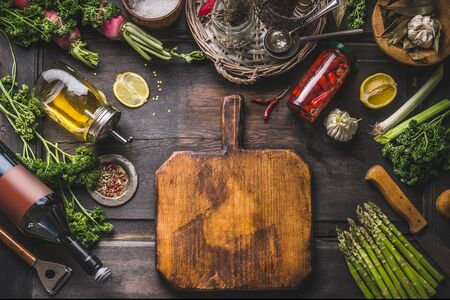 Food background. Various ingredients and seasonings for tasty cooking around  cutting board on wooden rustic table. Oil,lemon, vine bottle, pickled chili in jar, asparagus, herbs and spices. Frame Zdjęcie Seryjne - 147671768