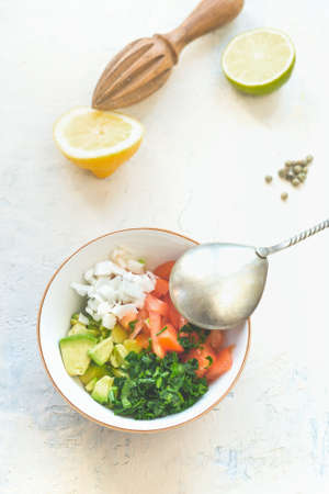 Bowl with spoon and fresh ingredients: avocado, coriander, tomato, onion. Lemon, lime, pepper and wooden citrus press in background. Healthy food concept in summer. White background. Top view Zdjęcie Seryjne - 153689437