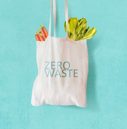 White cloth bag with inscription 'zero waste' filled with vegetables hanging in front of bright blue background. Ecological, sustainable concept. Front view